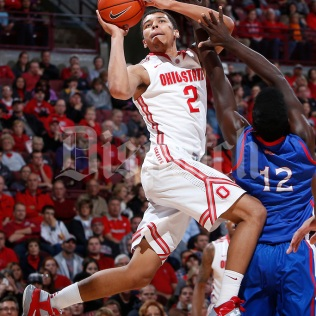 Ohio State Buckeyes forward Marc Loving (2) twists around to make a shot while guarded by American University Eagles forward Yilret Yiljep (12) during the first half of Wednesday's NCAA Division I basketball game at Value City Arena in Columbus on November 20, 2013. (Barbara J. Perenic/The Columbus Dispatch)