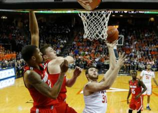 Virginia forward Jarred Reuter (31) takes a shot as Ohio State center Micah Potter, center, and Ohio State forward Marc Loving (2) defend during the first half of an NCAA college basketball game in Charlottesville, Va., Wednesday, Nov. 30, 2016. (AP Photo/Steve Helber)